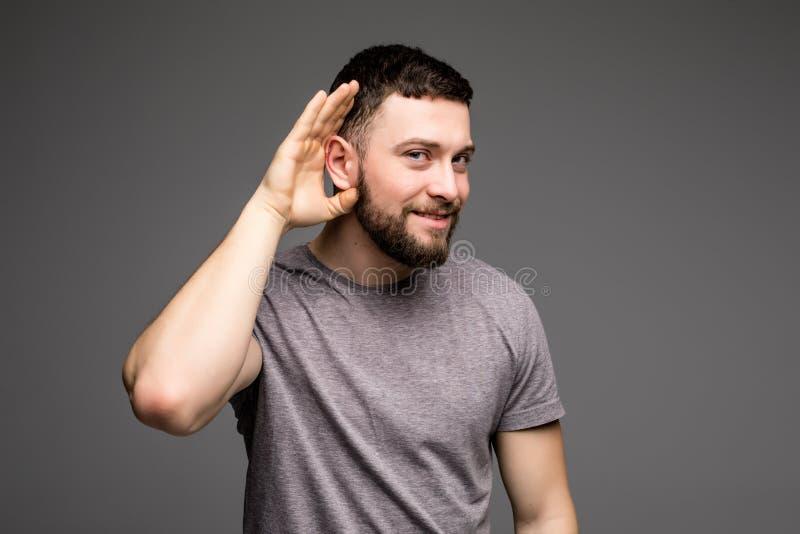 Le mâle de écoute tient sa main près de son oreille au-dessus de fond gris image stock