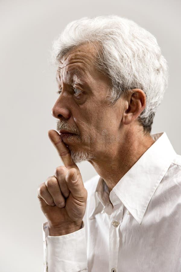 Le mâle effrayé sérieux garde le doigt antérieur sur des lèvres image stock