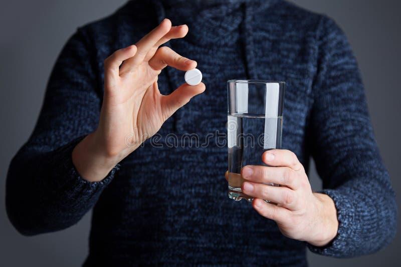 Le mâle juge un comprimé prêt à dissoudre la pilule dans l'eau images stock