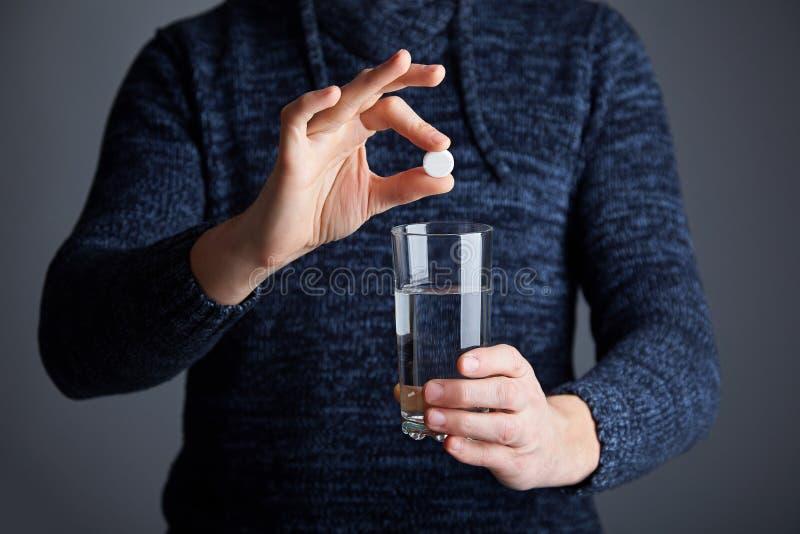 Le mâle juge un comprimé prêt à dissoudre la pilule dans l'eau photo libre de droits