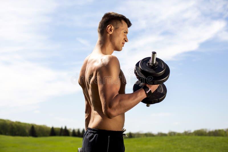 Le mâle musculaire est concentré sur des bras de formation en nature images libres de droits