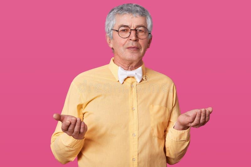 Le mâle plus âgé ne sait pas ce qu'un peu l'émotion à exprimer, soulève ses paumes  Vieil homme avec la chemise jaune et noir arr photos stock