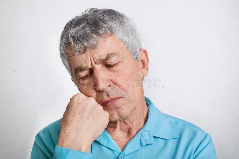 Le mâle plus âgé réfléchi avec l'expression songeuse, se sent seul, garde la main sous le menton et contemple au sujet de sa vie, images libres de droits