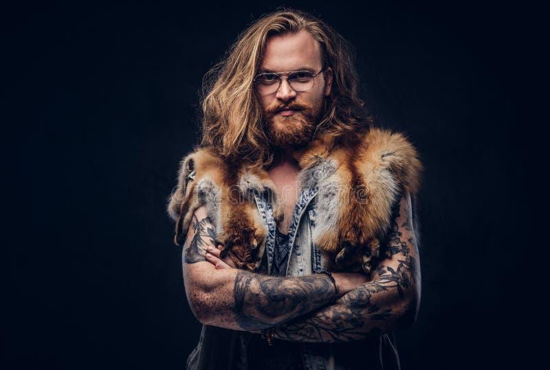 Le mâle roux de hippie de Tattoed avec de longs cheveux luxuriants et pleine barbe habillés dans un T-shirt et une veste tient la photographie stock