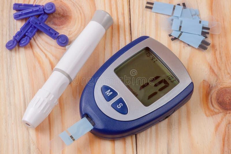 Le mètre de glucose sanguin sur un fond en bois clair image libre de droits