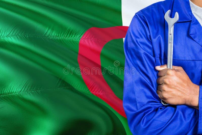 Le mécanicien algérien dans l'uniforme bleu tient la clé contre onduler le fond de drapeau de l'Algérie Technicien croisé de bras photo libre de droits