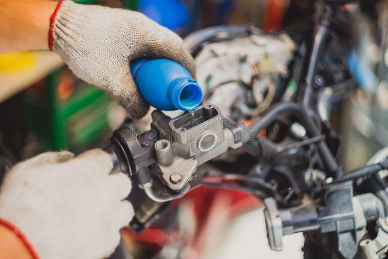 Le mécanicien Check et ajoutent le liquide des freins sur le réservoir de frein de moto image libre de droits