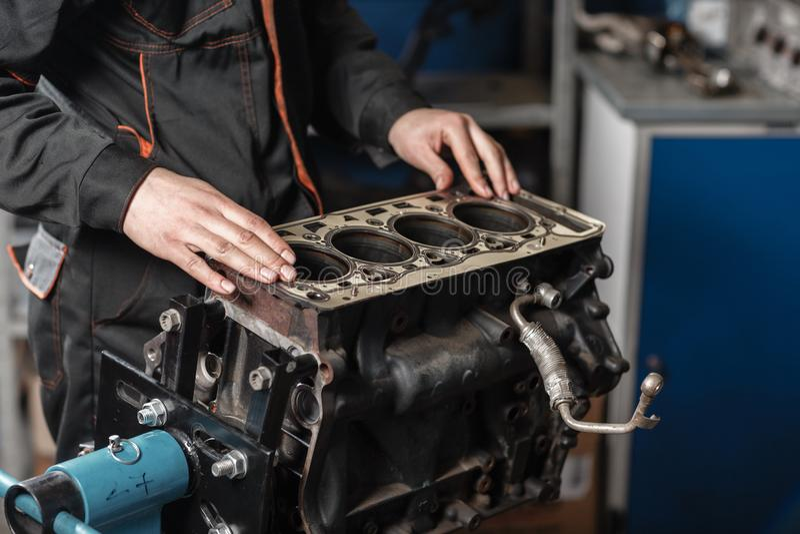 Le mécanicien démontent le véhicule de moteur de bloc Moteur sur un support de réparation avec le piston et la bielle de des véhi photographie stock libre de droits
