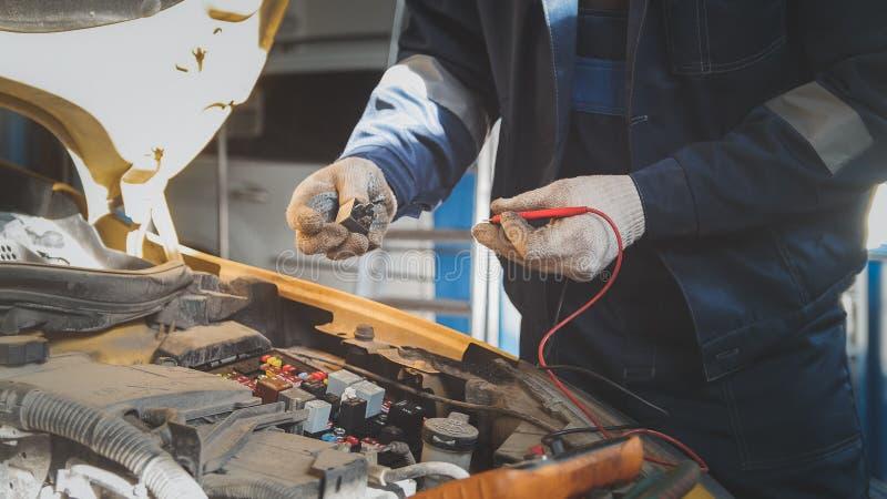 Le mécanicien dans l'atelier automatique travaille avec des électricités de voiture - câblage électrique, voltmètre photographie stock