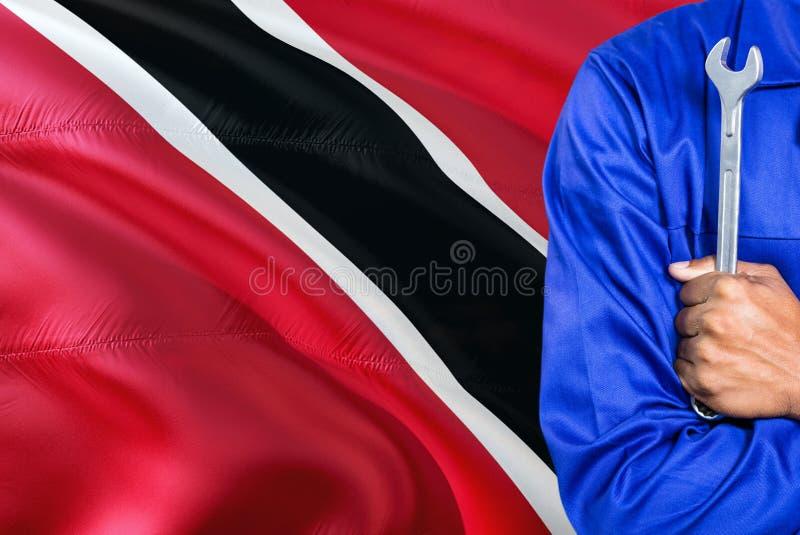 Le mécanicien dans l'uniforme bleu tient la clé contre onduler le fond de drapeau de Trinidad And Tobago Technicien croisé de bra images libres de droits