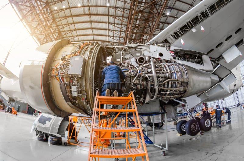 Le mécanicien de spécialiste répare l'entretien d'un grand moteur d'un avion de transport de passagers dans un hangar image libre de droits