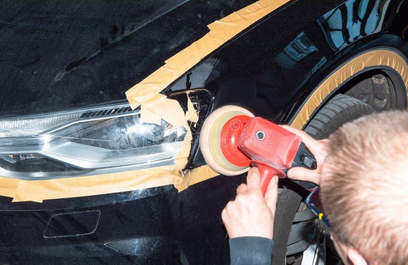 Le mécanicien de voiture polit la peinture sur le véhicule - atelier de réparation de Serie photos libres de droits