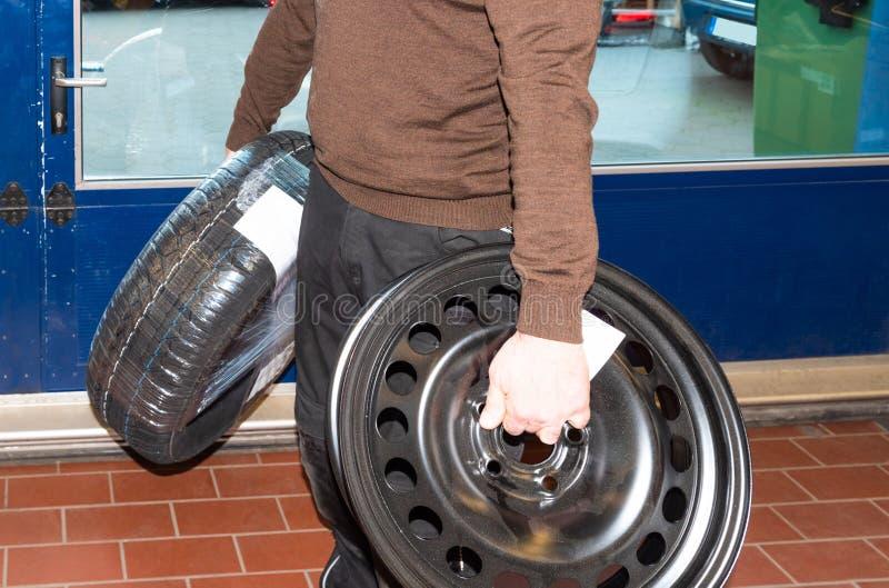 Le mécanicien de voiture porte les roues et les changements les pneus de voiture - atelier de réparation de Serie photos libres de droits