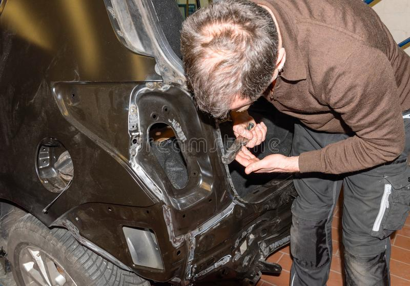 Le mécanicien de voiture répare des dommages d'accidents au véhicule dans une station service - atelier de réparation de voit photos stock