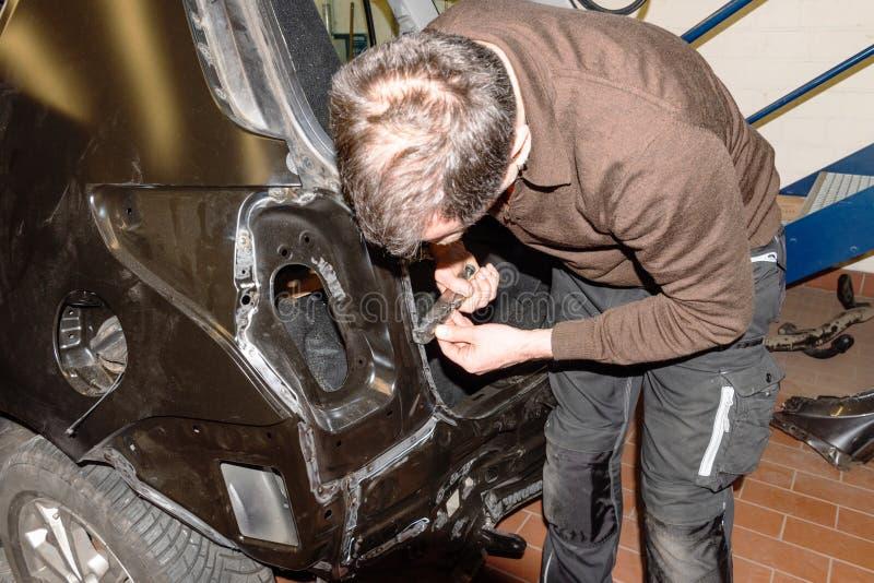 Le mécanicien de voiture répare des dommages d'accidents au véhicule dans une station service - atelier de réparation de voit photo libre de droits