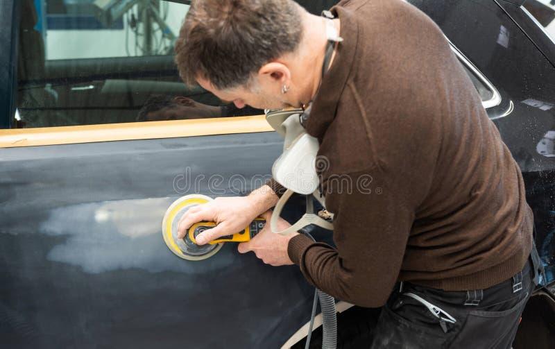 Le mécanicien de voiture rectifie une pièce de voiture en travail manuel dans une station service - atelier de réparation de voit photographie stock libre de droits