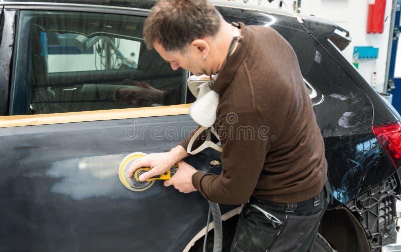 Le mécanicien de voiture rectifie une pièce de voiture en travail manuel dans une station service - atelier de réparation de voit photographie stock