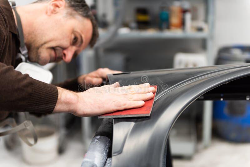 Le mécanicien de voiture rectifie une pièce de voiture en travail manuel dans une station service - atelier de réparation de voit photo stock