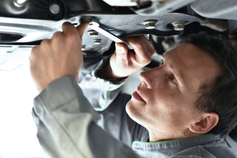 Le mécanicien de voiture travaille dans un atelier, réparation des voitures images stock