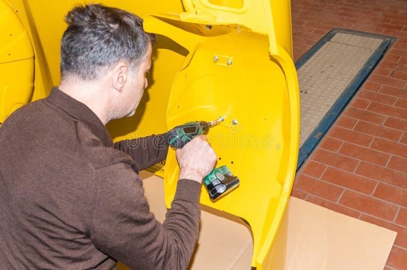 Le mécanicien de voiture visse des pièces de voiture ensemble encore après restauration - atelier de réparation de Serie images stock