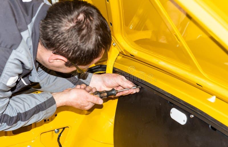 Le mécanicien de voiture visse des pièces de voiture ensemble encore après restauration - atelier de réparation de Serie photographie stock libre de droits