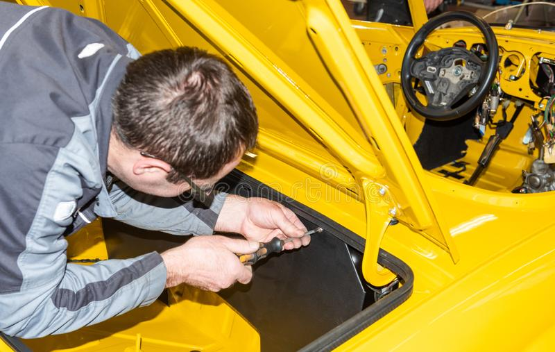 Le mécanicien de voiture visse des pièces de voiture ensemble encore après restauration - atelier de réparation de Serie images libres de droits