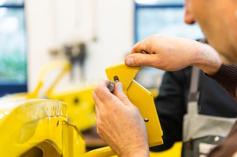 Le mécanicien de voiture visse des pièces de voiture ensemble encore après restauration - atelier de réparation de Serie photos stock