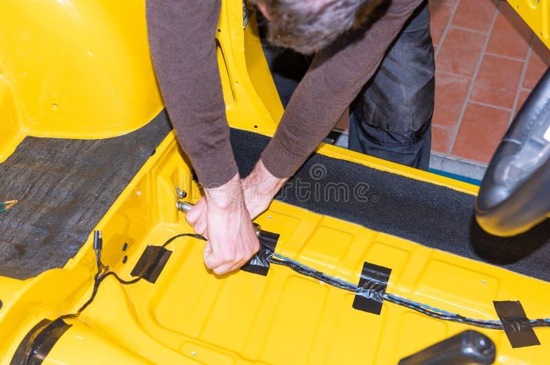 Le mécanicien de voiture visse des pièces de voiture ensemble encore après restauration - atelier de réparation de Serie image libre de droits