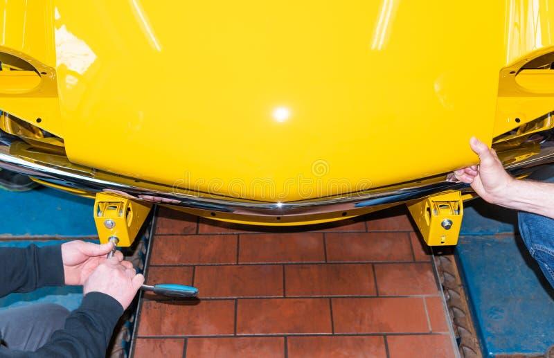 Le mécanicien de voiture visse des pièces de voiture ensemble encore après restauration - atelier de réparation de Serie image stock