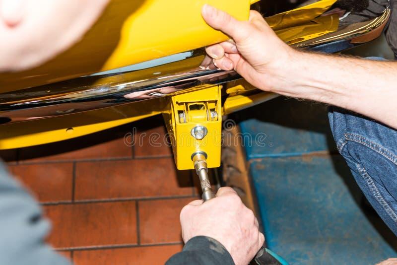 Le mécanicien de voiture visse des pièces de voiture ensemble encore après restauration - atelier de réparation de Serie photo stock