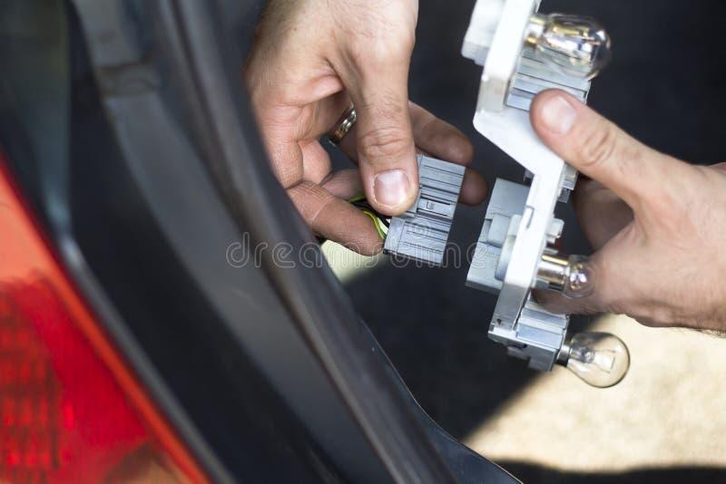 Le mécanicien enlève la lampe de cadre dans la voiture Cube électrique s'élevant photographie stock