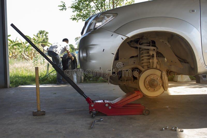Le mécanicien enlève les pneus de camion pick-up utilisant le cric rouge images libres de droits