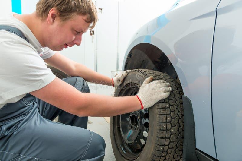 Le mécanicien installe sur les pneus d'hiver de voiture images libres de droits