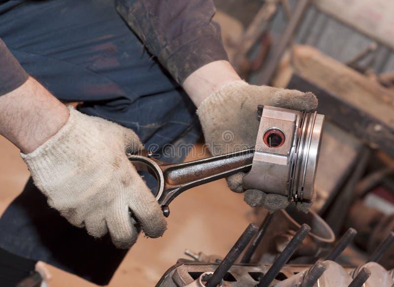 Le mécanicien juge le piston disponible images stock