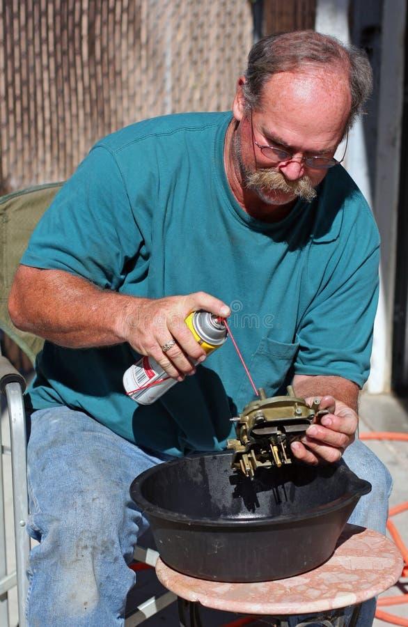 Le mécanicien nettoie le carburateur image stock