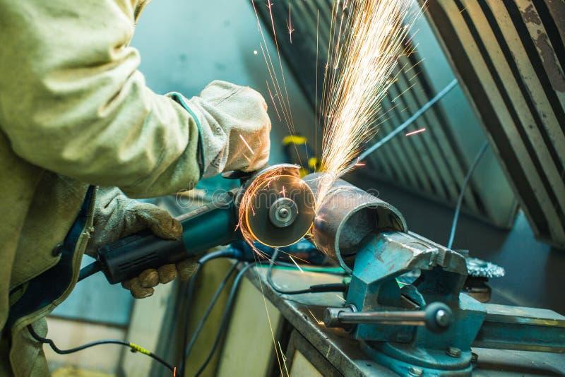 Le mécanicien nettoie une couture soudée sur une section d'un pépin en acier images stock