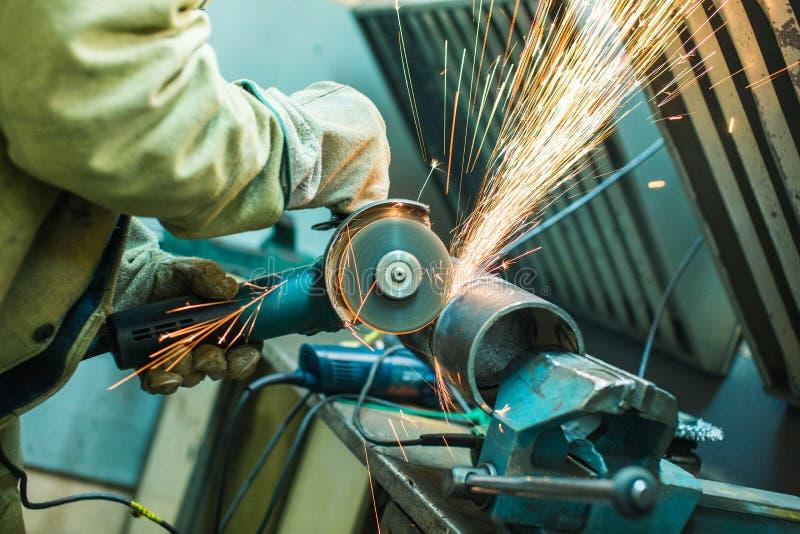 Le mécanicien nettoie une couture soudée sur une section d'un pépin en acier image stock