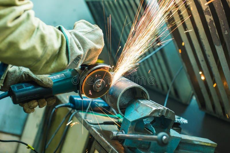 Le mécanicien nettoie une couture soudée sur une section d'un pépin en acier photographie stock libre de droits
