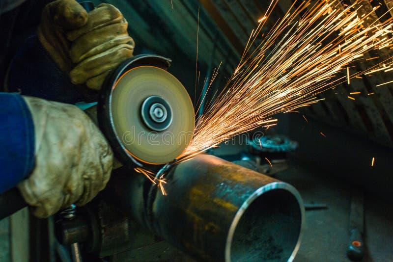 Le mécanicien nettoie une couture soudée sur une section d'un pépin en acier photos stock