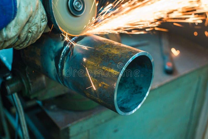 Le mécanicien nettoie une couture soudée sur une section d'un pépin en acier photo libre de droits
