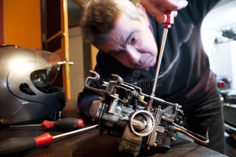 Le mécanicien répare un carburateur images libres de droits