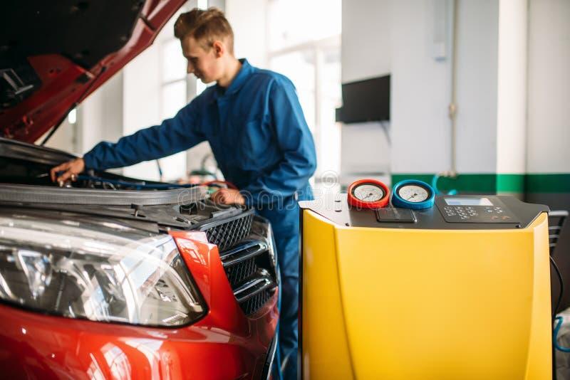 Le mécanicien vérifie le dispositif de climatisation dans la voiture photos stock