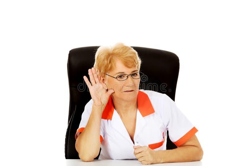 Le médecin ou l'infirmière féminin plus âgé de sourire s'asseyant derrière le bureau et surprend une conversation photo stock