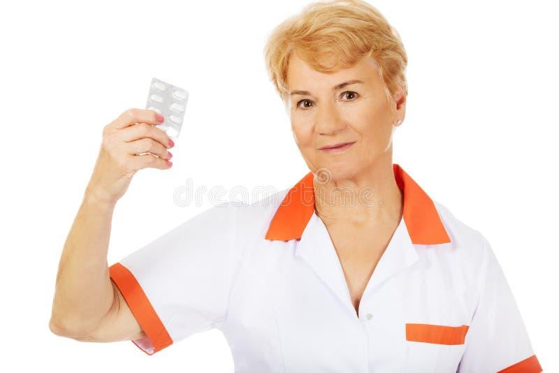 Le médecin ou l'infirmière féminin plus âgé de sourire tient la boursouflure des pilules photos libres de droits