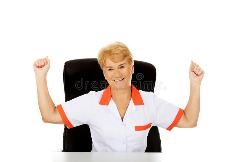 Le médecin ou l'infirmière féminin plus âgé heureux s'asseyant derrière le withd de bureau remet  images stock