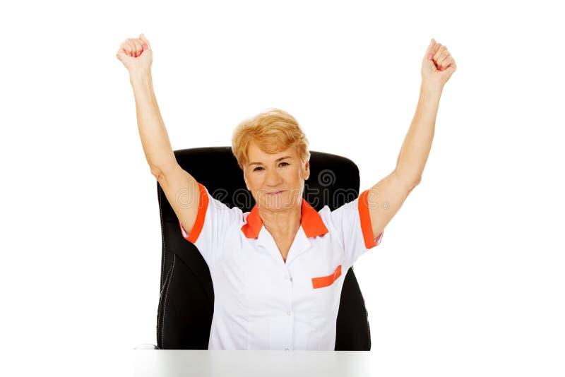 Le médecin ou l'infirmière féminin plus âgé heureux s'asseyant derrière le withd de bureau remet  image stock