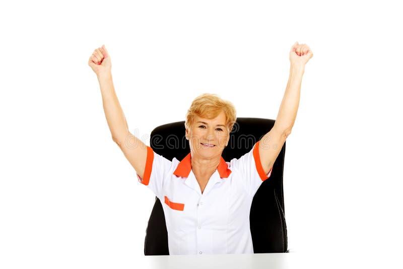 Le médecin ou l'infirmière féminin plus âgé heureux s'asseyant derrière le withd de bureau remet  photos libres de droits