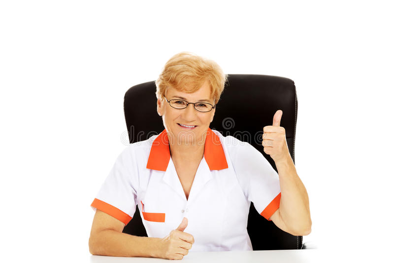 Le médecin ou l'infirmière s'asseyant derrière le bureau et les expositions femelle plus âgé de sourire manient maladroitement  photographie stock libre de droits