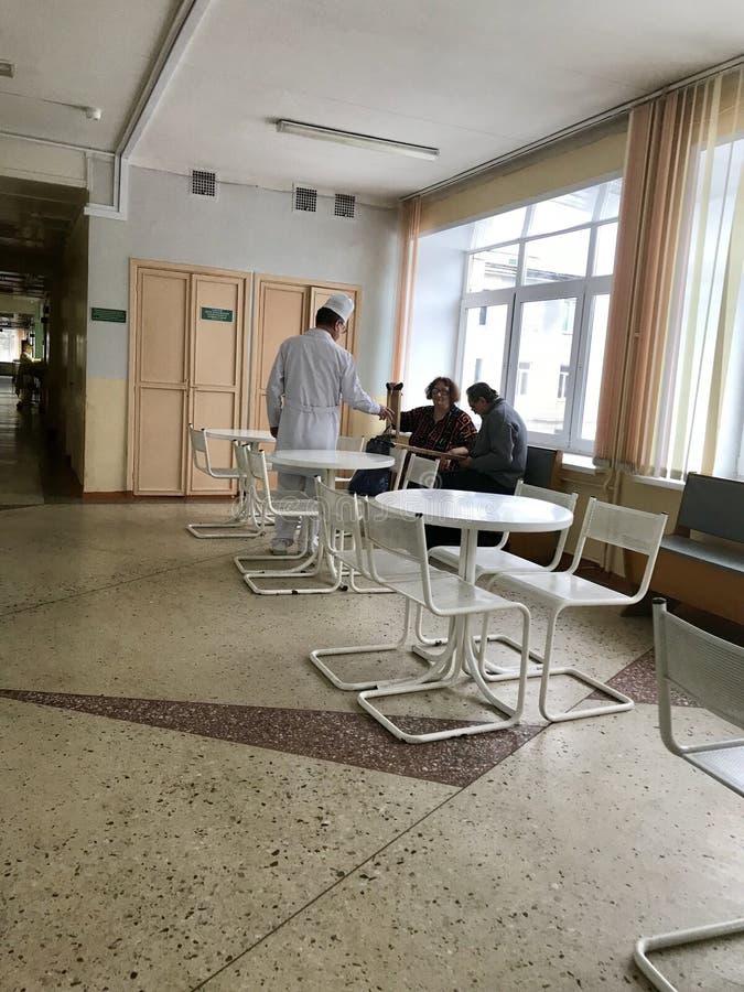 Le médecin traitant parle avec le patient de l'hôpital et le visiteur image stock