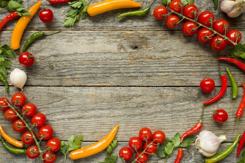 Le mélange de la tomate-cerise de poivre de piment sur un ail de branche et d'autres épices sur une copie en bois espacent le fon images libres de droits